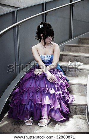 A young girl sits alone in her prom dress on a lonely flight of stairs.