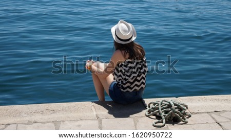 A young girl sits near the sea and looks into the distance. Relaxation, travel, relaxation.