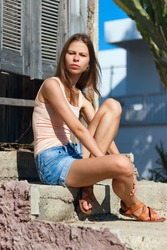 A young girl sits on the concrete steps at the entrance to a stylized inn, legs crossed, long hair fluttering, the girl is thinking about something