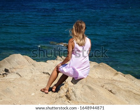 A young girl sits on the rocks and looks at the sea. Relaxation, travel, relaxation.