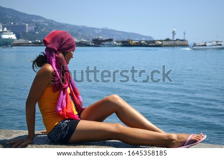 A young girl sits on the waterfront and enjoying the view of the sea. Beautiful woman in bandana sitting on stone and looks at ships and boats in the water of the ocean. Port city on the background