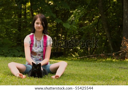 a young girl sitting in the grass with her cat midnight on a summer day with room for your text