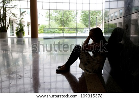 A young girl sitting on floor feeling devastated after hearing of bad news in her life.