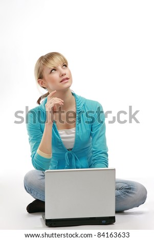 A young girl sitting on the floor with a laptop, looking up