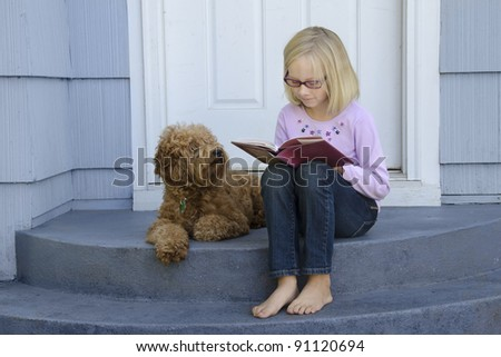 A young girl sitting on the front steps is engrossed in a book as her dog sits beside her