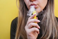 A young girl smokes disposable electronic cigarette. Bright yellow background