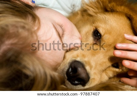 A young girl sound asleep and snuggled up with her Golden Retriever dog. - stock photo