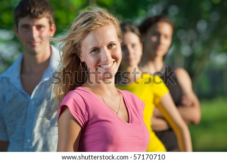 A young girl stands in a park on the background of their friends and girlfriends