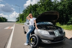 A young girl stands near a broken car with a broken wheel in the middle of the highway and is frustrated waiting for help on a hot day. Breakdown and breakdown of the car. Waiting for help.