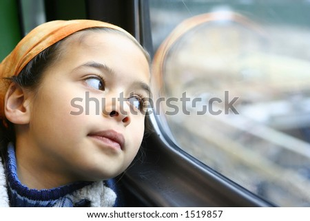 A young girl stares out of the window from a moving train, lost in her little world - stock photo