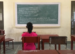 A young girl student looking at a blackboard with in the classom. A back view of a pupil in the classroom of an Indian school.
