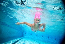 a young girl swimming free underwater in a swimmingpool
