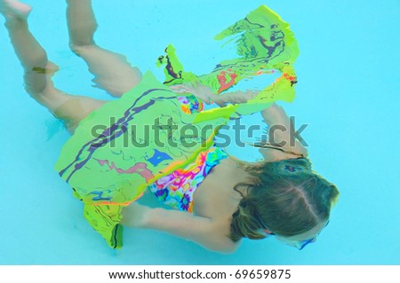 A Young girl swimming through a hoop under water.
