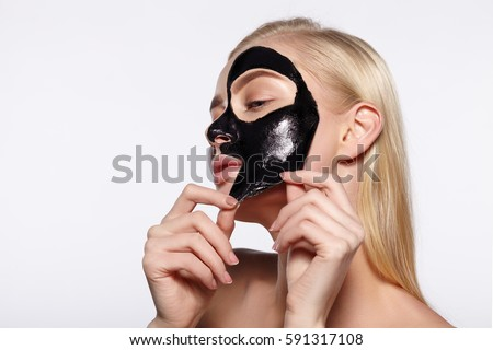 A young girl takes a black mask from her face. The gray background. #591317108
