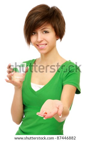 A young girl taking pills, isolated on white