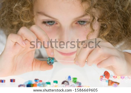 A young girl threading beads onto a thread