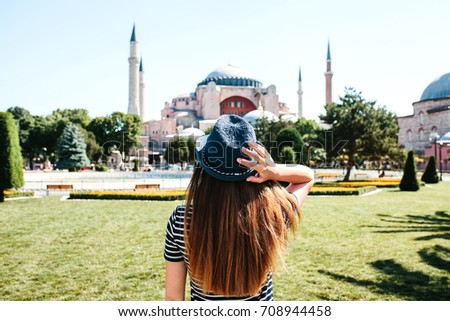 A young girl traveler in a hat from the back in Sultanahmet Square next to the famous Aya Sofia mosque in Istanbul, Turkey. Travel, tourism, sightseeing. #708944458