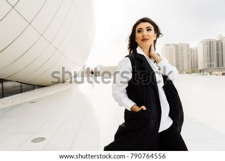a young girl walks in the modern district of the city