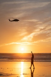 A young girl waves to a helicopter passing overhead on Mission Beach, San Diego, California