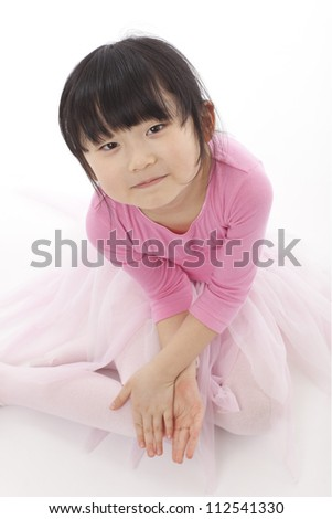A young girl wearing a pink tutu shot in the studio against a white background.