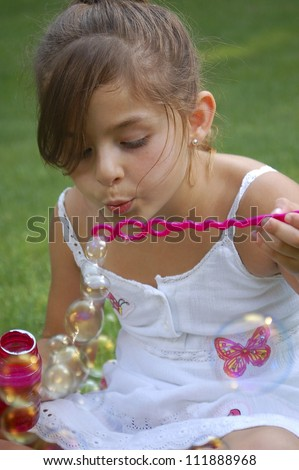 A young girl, wearing a white butterfly dress, blows bubbles outside.