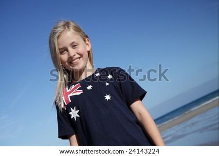 A young girl wearing an Australian flag t-shirt at the beach.