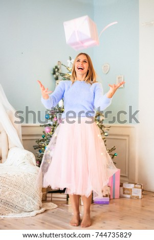 A young girl, white hair in a blue mohair sweater and a pink skirt-tutu throws up a gift and laughs. for the new year in a stylish cozy studio room with a decor and a Christmas tree with pastel tones