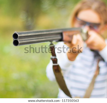 A young girl with a gun for trap shooting and shooting glasses aiming at a target. Short depth of field, focus on the barrel