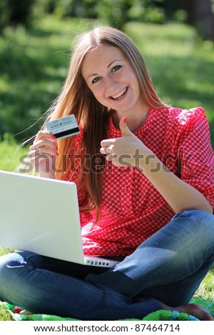 A young girl with a laptop and a credit card at summer park? - stock photo