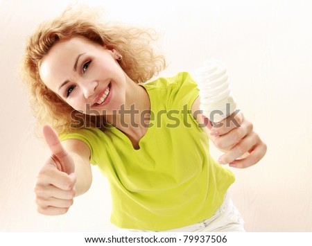 A young girl with an energy-saving bulb and showing ok, isolated on white