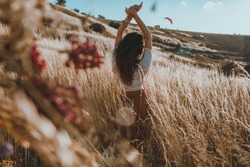 A young girl with black hair is standing with her back in a meadow in a skirt and a white blouse looking at the sunset, raising her arms upwards Concept - freedom and unity with nature