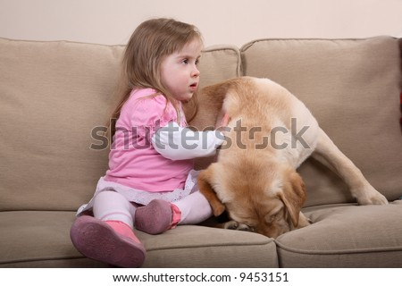 A young girl with Down Syndrome sitting on a couch with a puppy. A form of therapy.