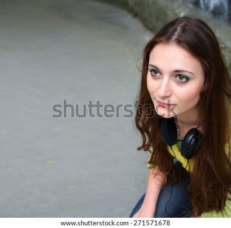 A young girl with headphones hanging at your neck. Free space for a text