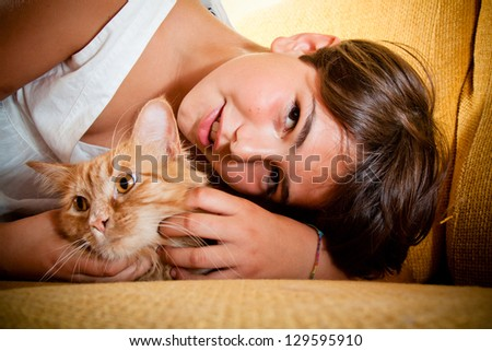A young girl with her long-haired ginger cat.