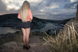 A young girl with long blond hair stands with her back in short black shorts, peers into the bay from the rocks at sunset