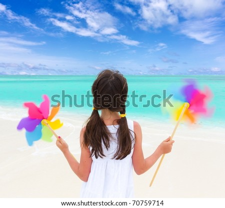 A young girl with windmills on the beach.