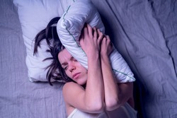 A young girl woke up in the morning in bed with a severe headache after the stress at work and nerves. The woman has insomnia and discomfort, feeling pain.