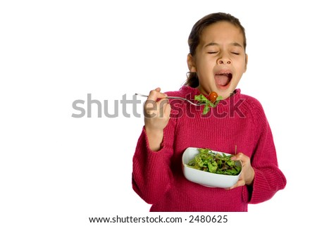 A young girl yawning showing boredom at having to eat her bowl of fresh salad, isolated on white. Concept : Healthy eating.