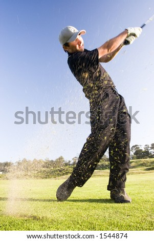 A young golfer hits the ball sending grass flying into the air (motion blur)