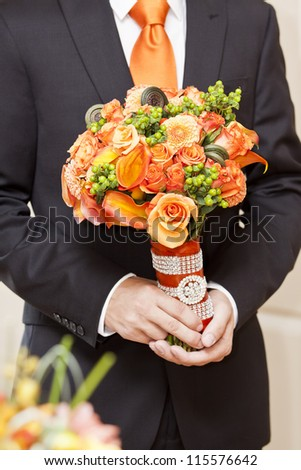 A young groom holding bouquet of flowers