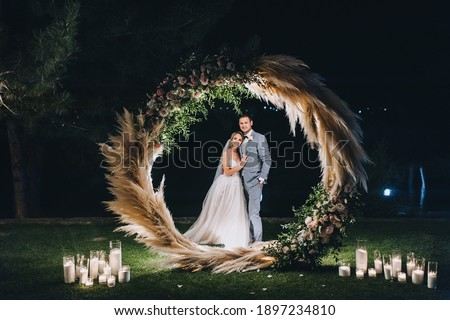 A young groom in a gray suit and a cute, smiling blonde bride embrace, standing on the green grass, near a round wooden arch decorated with reeds, flowers, candles. Night wedding portrait. Foto stock ©