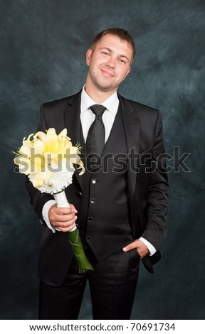 A young groom with a bouquet in studio