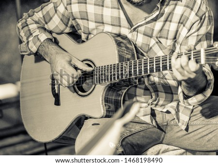 A young guitarist in a checkered shirt, he performs with acoustic guitar, a vintage monochrome image.