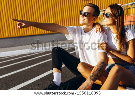 A young guy and a girl, a guy points his finger at something in the distance, sitting on the asphalt in the city against a yellow wall. Shopping concept