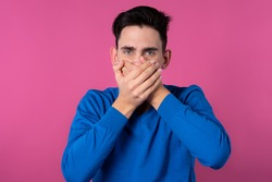 A young guy in a blue sweater. Don't speak evil. Do not listen to evil. Do not speak evil. Pink background.