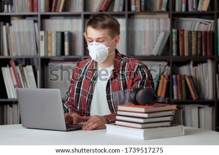 A young guy in a surgical mask is working on a laptop in the library at a safe distance from other people. Stock photo ©