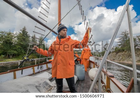 A young guy in the North Sea in a fisherman's overalls is about to cast a bait on a fishing rod hook overboard #1500606971