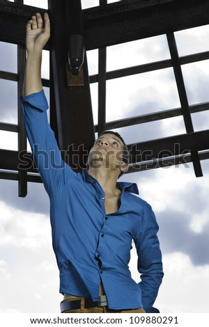 A young guy is faithfully looking up, stretching his arm toward the sky.