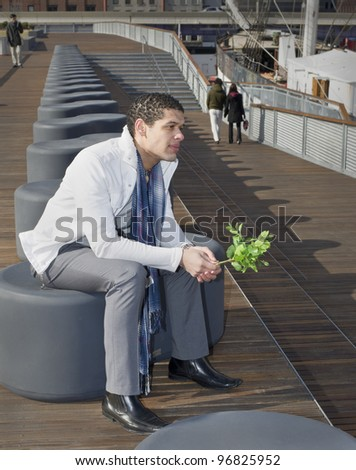 A young guy is holing a bunch of green plants, sitting outside, thinking and waiting…/Waiting for you
