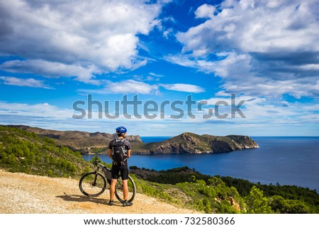a young guy on a mountain bike trails in Spain and takes a photo on a white phone in the background of the Mediterranean sea of the Costa Brava.  mountain road near the city of Cadaques